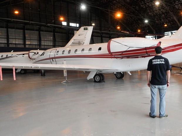 Auditor da Receita Federal observa aeronave em Campinas (Foto: Divulgação/Receita Federal)