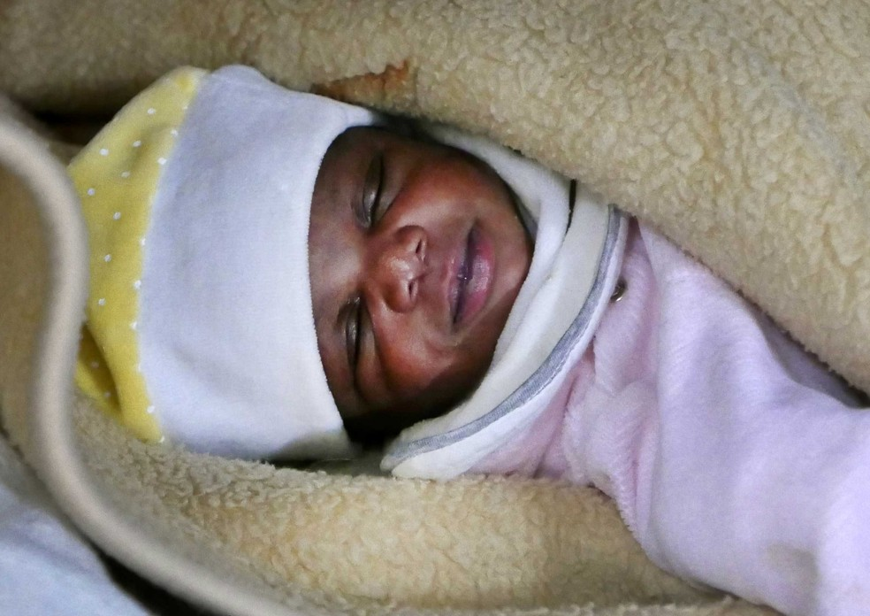 Bebê dorme após ser resgata durante travessia do Mediterrâneo, neste domingo (2)   (Foto: Yannis Behrakis/ Reuters)