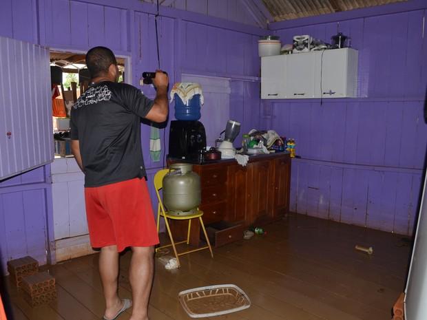 Casa no bairro Quinze, em Rio Branco, nunca tinha alagado; José olha a sujeira deixada pela água  (Foto: Aline Nascimento/G1)