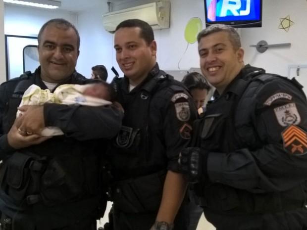 Policiais com menino encontrado em caixa de papelão embaixo de um veículo  (Foto: UPP )