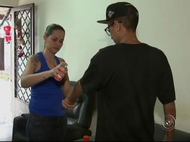 Professora faz questão de borrifar spray para espantar mosquitos dos filhos (Foto: Reprodução/TV TEM)