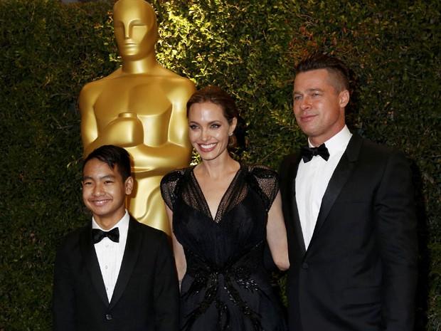 Angelina Jolie entre o marido, Brad Pitt, e um de seus filhos, Maddox, na noite deste sábado (16) (Foto: Fred Prouser/Reuters)