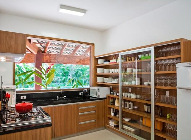Cozinha | O espaço ganhou armários abertos para facilitar a circulação. Os móveis de madeira freijó foram desenhados pela dupla Olegário de Sá e Gil Cioni (Foto: Divulgação)