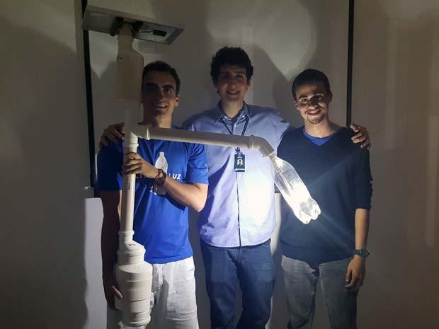 """Integrantes do projeto """"Um litro de luz"""" com poste aceso (Foto: Luciana Amaral/G1)"""