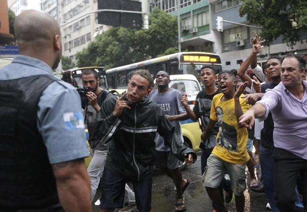 Manifestantes protestam e gritam com um policial após o enterro de Douglas Rafael da Silva Pereira, o DG (Foto: Ricardo Moraes/Reuters)