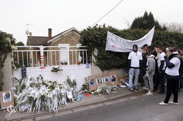 Dezenas de jovens deixaram flores e mensagens ao lado da casa onde foram mortos Laurent, de dez anos, Gnilane, de 14, e Valentin, de 16 (Foto: Patrick Kovarik/AFP)