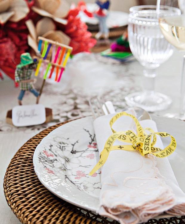 A fita de bênçãos amarra o guardanapo. Sousplat de ratã e taças Cecilia Dale (Foto: Lufe Gomes / Editora Globo)