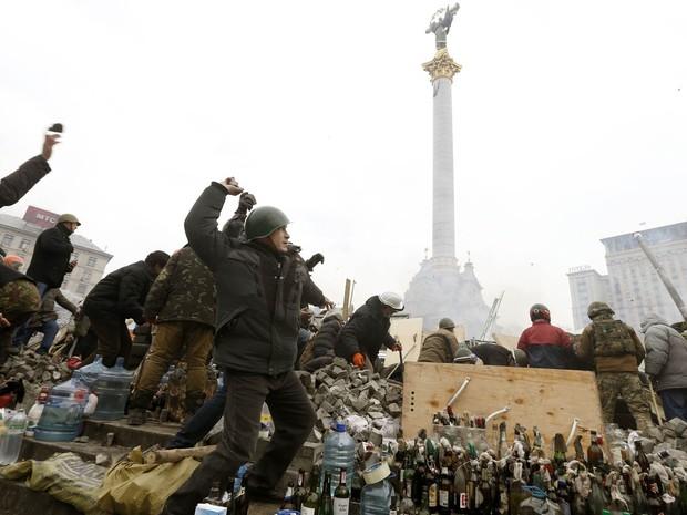 19/2 - Jovens atiram pedras contra a polícia, com diversas garrafas de coquetel molotov preparadas no chão, na Praça da Independência, em Kiev (Foto: Vasily Fedosenko/Reuters)