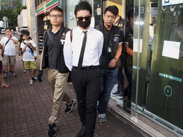 Um funcionário do Uber é levado pela polícia durante uma operação no escritório da empresa em Hong Kong, China. Cinco motoristas foram presos por 'uso ilegal de veículos de aluguel'  (Foto: Apple Daily/Reuters)