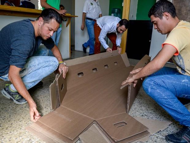 Homens dobram um caixão de papelão em Barquismeto, na Venezuela (Foto: Federico Parra/AFP)