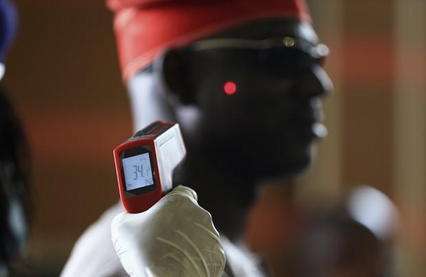 Homem tem a temperatura aferida em termômetro digital no aeroporto internacional de Abuja, na Nigéria   (Foto: Reuters/Afolabi Sotunde)