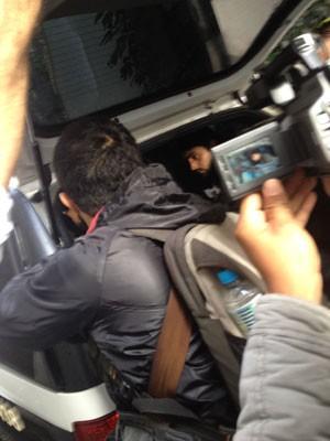 Raphael Sanz Casseb, ao fundo, foi preso por suspeita de dano ao patrimônio. 'Me respeitem', respondeu o jornalista ao ser indagado se havia participado de vandalismo (Foto: Kleber Tomaz / G1)