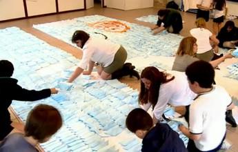 Crianças montam camisa uruguaia de quatro metros com barcos de papel