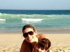 Ex-Paquita Cátia Paganote exibe boa forma em dia de praia com a filha