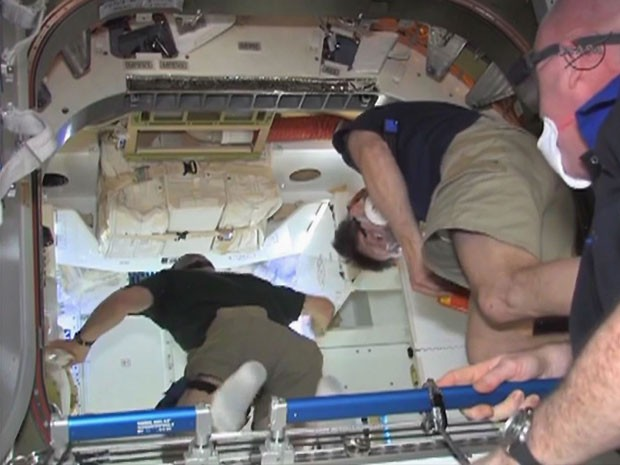 Astronautas entram na cápsula Dragon, acoplada à Estação Espacial (Foto: Nasa/Reuters)