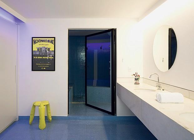 Mistura de closet e banheiro da suíte, esta área possui o armário de um lado e a bancada de mármore Carrara do outro. Repare na iluminação azul e branca de lâmpadas fluorescentes embutidas nas molduras de gesso no teto. Banqueta amarela da Conceito Firma  (Foto: Maíra Acayaba)