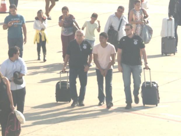 Suspeito chega acompanhado de dois delegados  (Foto: Reprodução/TV Clube)