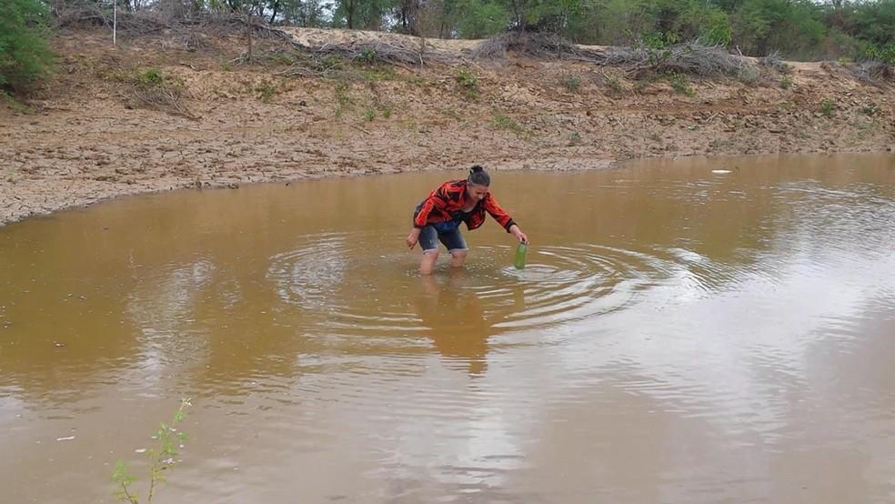 Maria das Graças levou água do rio em uma garrafa para mostrar a filha, em Cabacerias, na Paraíba (Foto: Artur Lira / G1)