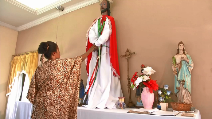 """Moradora da região adorando ao """"Santo Fujão"""" (Foto: TV Morena)"""