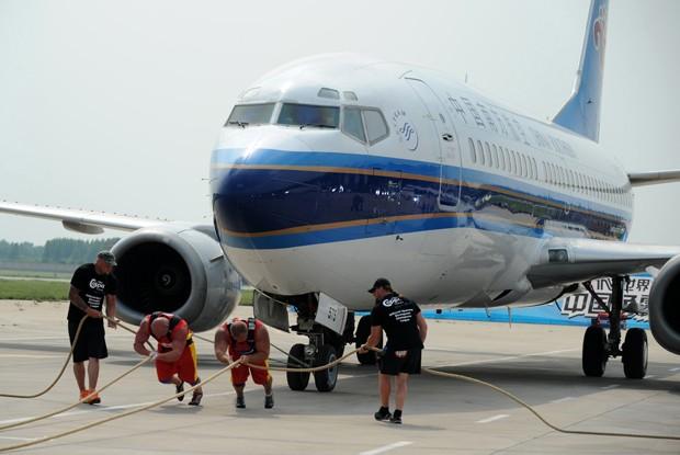 Dupla tenta puxar boeing durante campeonato de força na China (Foto: AFP)