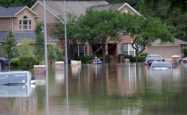 Homem usa barco em área inundada em Spring, no Texas  (Foto: David J. Phillip/AP)