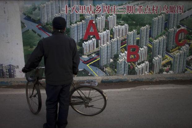 Chinês observa a propaganda de um empreendimento imobiliário. O PIB da China cresceu 7,8%, menor resultado em 13 anos (Foto: Alexander F. Yuan/AP)