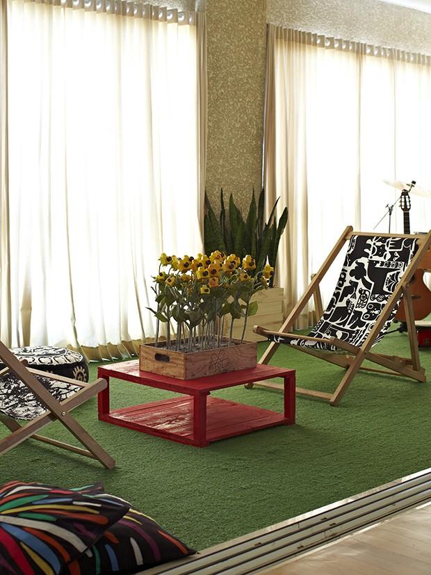 Fechada com janelas antirruído, a espaçosa varanda é coberta por um tapete de grama sintética. Por estar integrada à sala, ela funciona como playground não apenas das crianças, mas também dos pais. Projeto da arquiteta Bruna Riscali (Foto: Victor Affaro/Casa e Jardim)