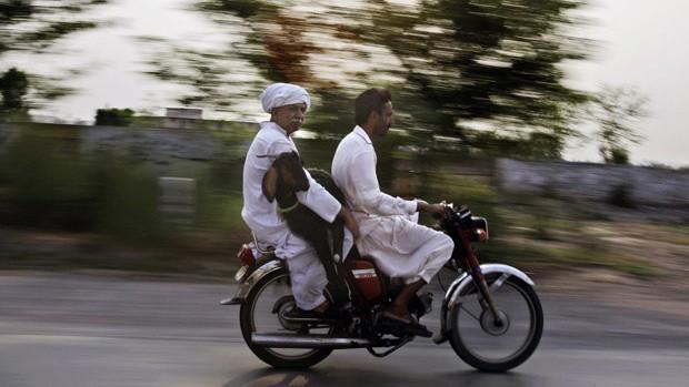 Homem segura bode na garupa de moto na periferia de Lahore, no Paquistão, nesta quarta-feira (22). O flagrante foi feito pelo fotógrafo Muhammed Muheisen (Foto: AP)