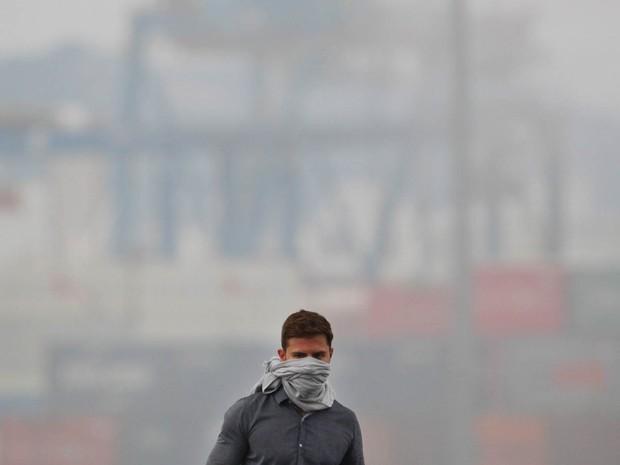 Homem usa pano como máscara durante incêndio no pátio de cargas do terminal alfandegado da Localfrio, na margem esquerda do Porto de Santos, em Guarujá, litoral sul de São Paulo (Foto: Clayton de Souza/Estadão Conteúdo)