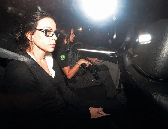 Acompanhada de policial  Adriana  Ancelmo ´levada para prisão domiciliar.As joias  se foram,mas sua privada tem assento aquecido (Foto:  Marcelo Theobald / Agência O Globo)