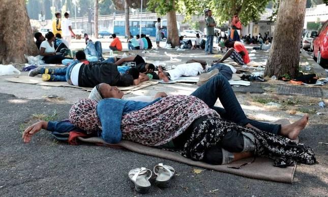 Refugiados descansam debaixo de árvores, numa praça de Roma (Foto: Alberto Pizzoli / AFP)
