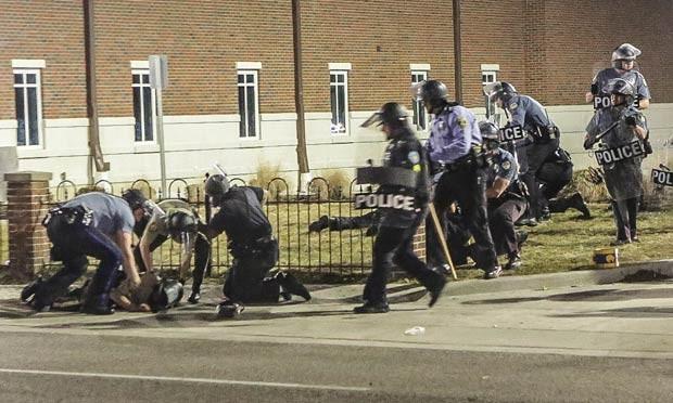 Policiais socorrem um colega atingido por um tiro em frente ao Departamento de Polícia de Ferguson, Missouri (EUA) (Foto: Lawrence Bryant/St. Louis American/Reuters)