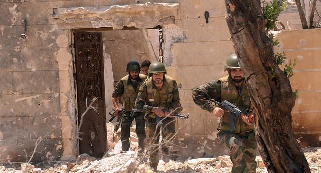 As forças leais ao presidente Bashar al-Assad durante confronto contra os rebeldes, em Aleppo, na Síria (Foto: AP Photo/SANA)
