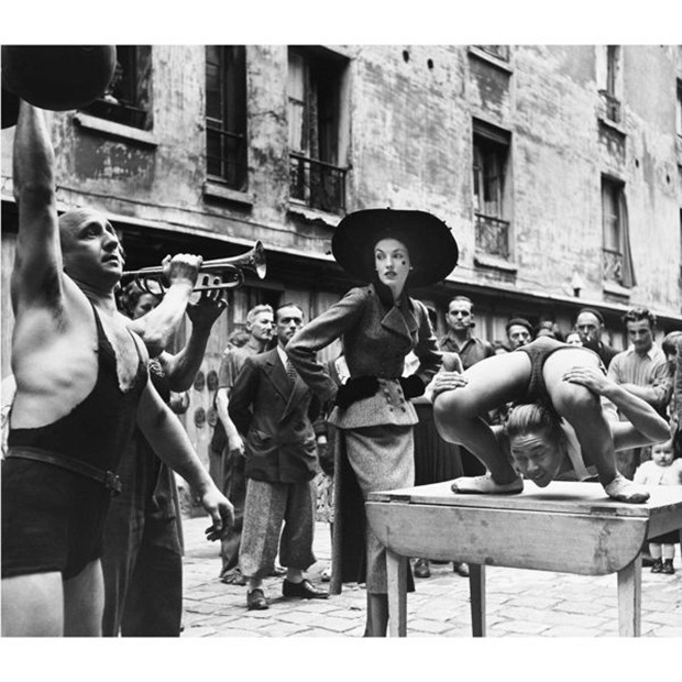 Elise Daniels with street performers, Le Marais, Paris, 1948. Suit by Balenciaga (Foto: PHOTOGRAPH BY RICHARD AVEDON © THE RICHARD AVEDON FOUNDATION)