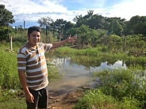 Jacob Castro Sarmento mostra o trajeto alagado de oito famílias para chegar em casa (Foto: Ivanete Damasceno/G1)