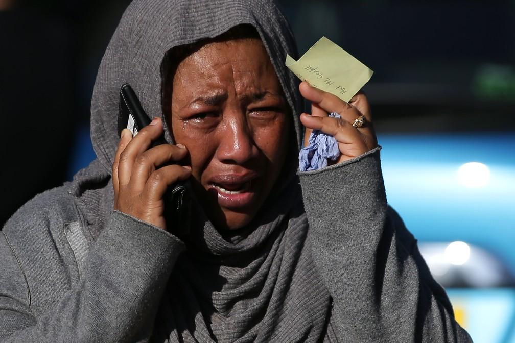 Mulher chora ao telefone enquanto tenta localizar parente que vivia em edifício atingido por incêndio em Londres (Foto: Daniel Leal-Olivas/AFP)
