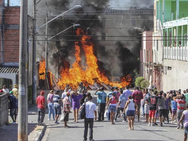 Moradores observam fogo em barricada montada para tentar conter policiais durante operação de reintegração de posse do Conjunto Residencial Caraguatatuba, em Itaquera, zona leste de São Paulo. (Foto: Marcos Ambrósio/Estadão Conteúdo)