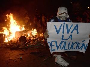 Manifestante com o rosto coberto segura cartaz que diz 'Viva a revolução' durante manifestação no Rio de Janeiro (Foto: Luis Gene/AFP)