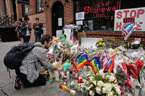 Homem presta homenagem em frente ao Stonewall Inn, em Nova York, em 16 de junho. (Foto: Julie Jacobson/AP)