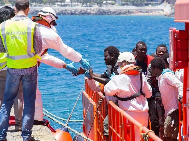 Imigrante recebe ajuda de funcionário para desembarcar nesta segunda-feira (30) no porto de Arguineguin, nas ilhas Canárias, Espanha (Foto: REUTERS/Borja Suarez)