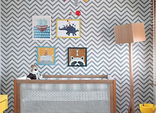 Toda a decoração deste quarto teve início a partir da escolha do papel de parede em zique-zague. Os quadros cheios de cor colocados na parede fazem o ambiente divertido, assim como o móbile acima do berço. Projeto do escritório Trix Interiores  (Foto: Evelyn Müller/Editora Globo)
