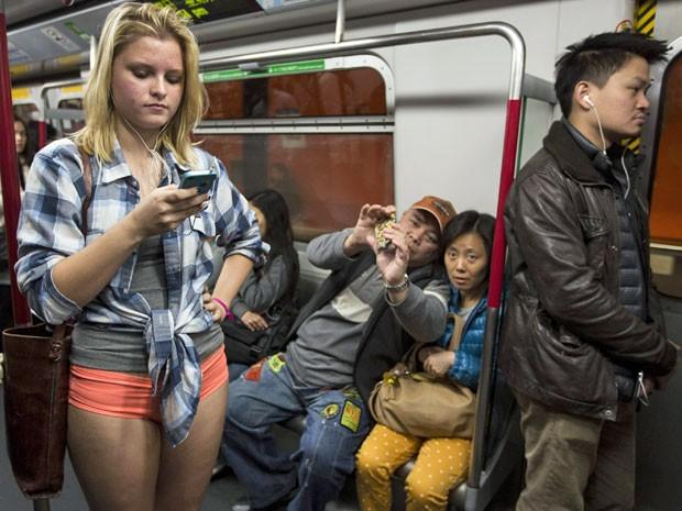 Mulher entra no metrô sem calça e chama atenção as pessoas que a fotografam  (Foto: Tyrone Siu/ Reuters)