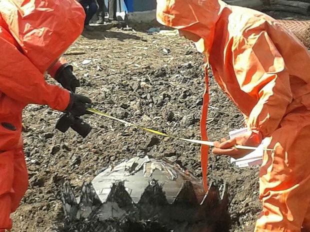 Homens examinam detritos espaciais que caíram na China, na cidade de Qiqihar (Foto: AFP Photo)