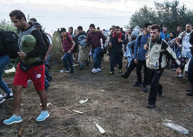 Migrantes atravessam fronteira entre Hungria e Servia, perto de Roszke, a 180 km de Budapeste, nesta terça-feira (25) (Foto: Sandor Ujvari/MTI via AP)