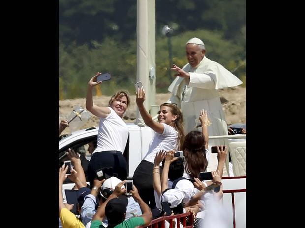 Mulheres tiram selfies com o Papa Francisco ao fundo na chegada do pontífice para celebrar uma missa em Guayaquil, no Equador (Foto: Jose Miguel Gomez/Reuters)