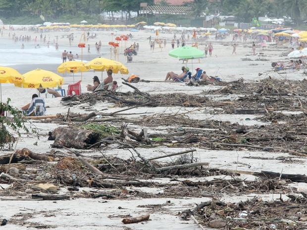 Turistas aproveitam o dia em meio a sujeira que o rio jogou no mar devido as fortes chuvas dos últimos dias na Praia de Maresias, no litoral de São Paulo (Foto: Márcio Fernandes/Estadão Conteúdo)