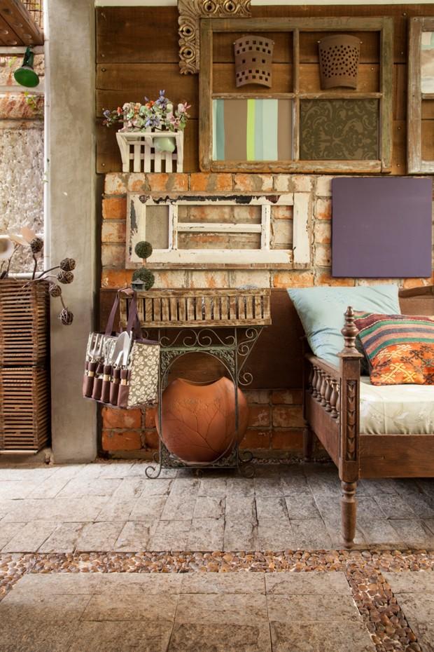 Uma das paredes ganhou uma composição de esquadrias antigos. Como fica na parte fechada do jardim, um confortável sofá-cama convida a ver a vida passar por ali (Foto: J. Vilhora/Divulgação)