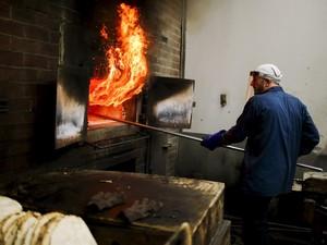 Um funcionário da padaria Chareidim Shmurah Matzoh prepara o pão matzoh para os feriados judaicos no bairro do Brooklyn, em Nova York, nos Estados Unidos (Foto: Eduardo Munoz/Reuters)