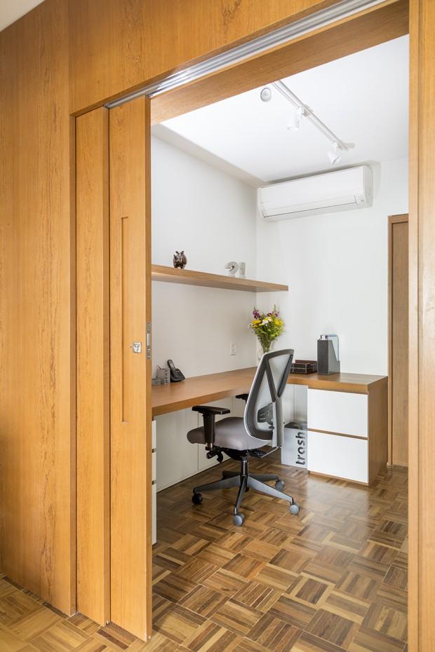 HOME OFFICE | Mesa, prateleiras e porta de madeira natural cumaru, cor mel, desenhadas pelo escritório Tria Arquitetura. Cadeira já pertencia ao acervo da família  (Foto: Julia Ribeiro/Divulgação)
