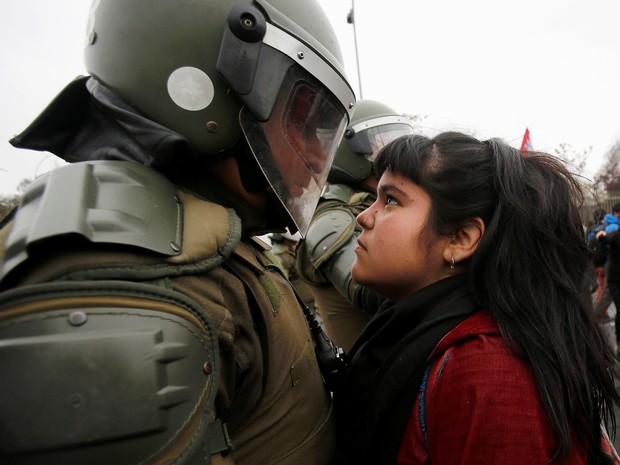 Jovem encara policial em Santiago neste domingo (11) (Foto: Carlos Vera/Reuters)